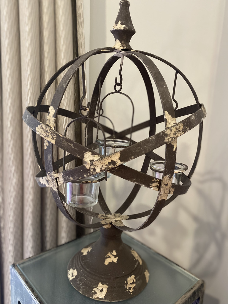 Rustic style metal tealight globe with stand sold by Mackenzie Paige Interiors.